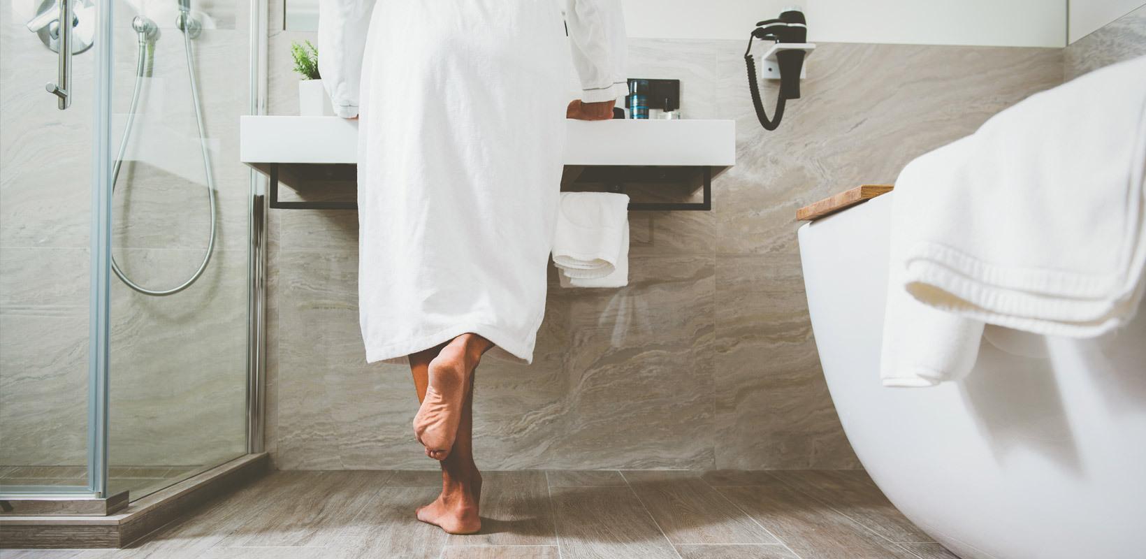 Siistissä kylpyhuoneessa seisova henkilö